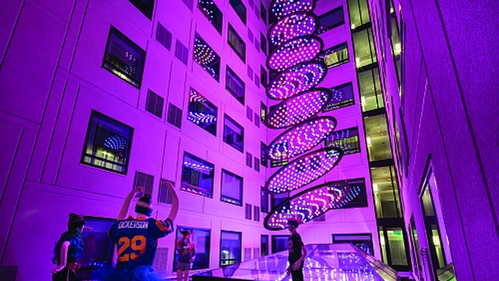"""In the millennial-targeted Moxy hotel in San Diego's Gaslamp Quarter, guestrooms surround a courtyard-like space where an LED-based architainment feature rises from the hotel lobby below through a glass ceiling, delivering dynamic shows conceived to evoke images such as a stream or waterfall. The dynamic RGB-LED-based system was created by Moment Factory and crafted by Digital Ambiance to be a """"hero centerpiece fixture"""" to be enjoyed by guests. (Photo credit: J Street Hospitality.)"""