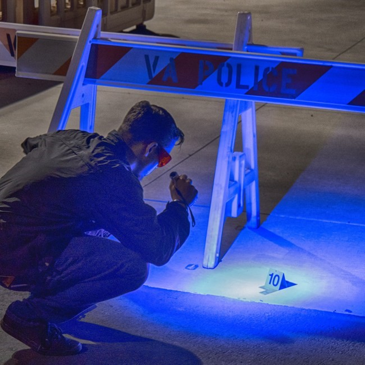 Forensic specialist uses a FoxFury HammerHead Forensic Light System to examine evidence in the field.